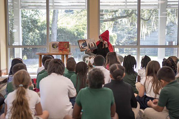 Librarian reading a book to a group of children