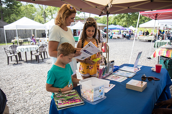 Adult and kids looking at library materials at a Farmers' Market